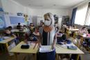 A teacher, wearing a protective face mask, teaches to schoolchildren in her classroom at the Magnolias primary school during its reopening in Nice as French children return to their schools after the summer break with protective face masks and social distancing as part of efforts to curb a resurgence of the coronavirus disease (COVID-19) across France, September 1, 2020. REUTERS/Eric Gaillard