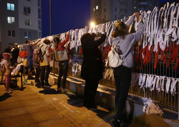 Les citoyens attachent des rubans blancs et rouges à une clôture, sur une place rebaptisée «des changements», à Minsk, le 15 septembre.