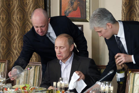 FILE - In this Friday, Nov. 11, 2011, file photo, businessman Yevgeny Prigozhin, left, serves food to Russian Prime Minister Vladimir Putin, center, during dinner at Prigozhin's restaurant outside Moscow, Russia. The U.S. sought to punish Russia on Monday, Sept. 30, 2019, for interfering with the November 2018 election by placing the yacht and private planes of a Russian financier, Yevgeny Prigozhin, on an international sanctions list along with employees of the Internet Research Agency that he has funded to spread false information on social media. (AP Photo/Misha Japaridze, Pool, File)