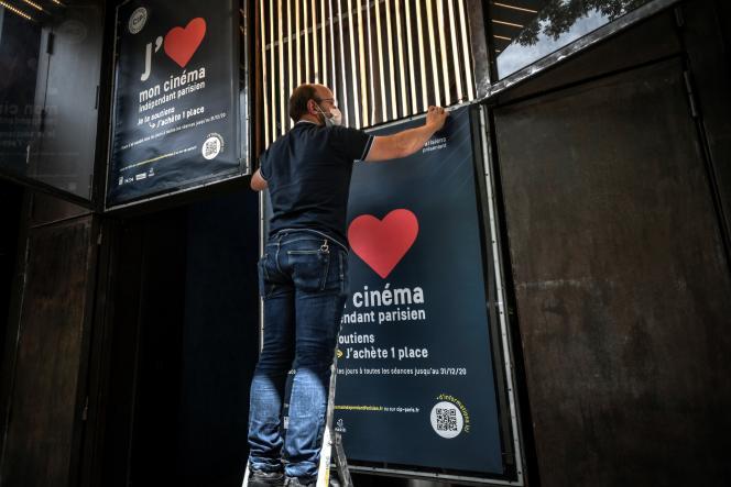 Un employé d'un cinéma parisien placarde des affiches qui appellent au soutien du secteur, en pleine crise due au coronavirus, le 18 juin.