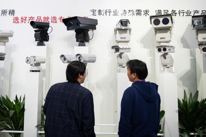 Des visiteurs regardent des caméras de reconnaissance faciale lors d'un salon consacré à la sécurité, à Pékin, en Chine, en octobre 2018.