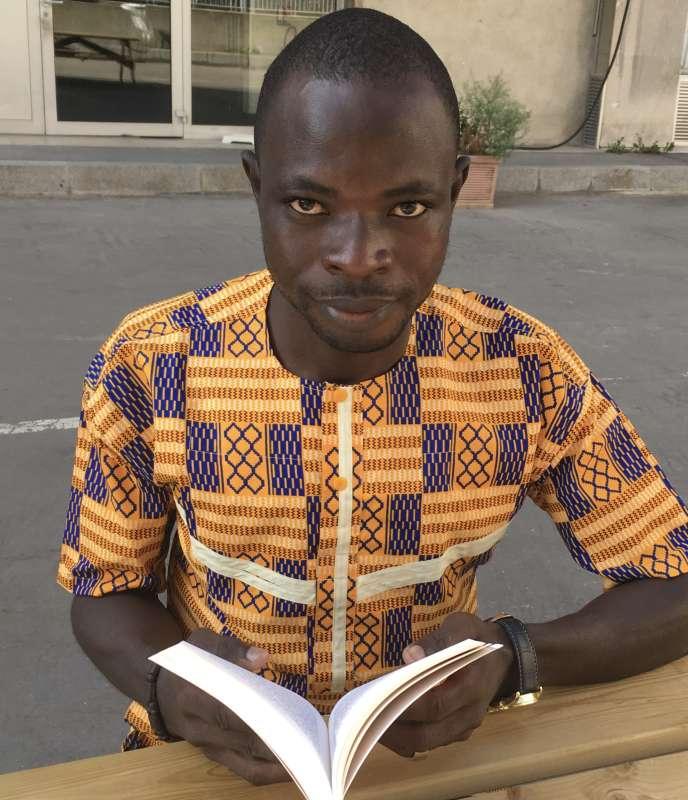 Yaya Diomandé feuillette« Abobo Marley»,son premier roman, dans la cour de la Cité internationale des arts, à Paris, le 17 septembre 2020.