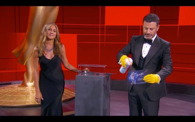 L'actrice Jennifer Aniston rejoint Jimmy Kimmel sur la scène du Staples Center le 20 septembre. Ils désinfectent une enveloppe contenant des résultats des Emmy Awards.