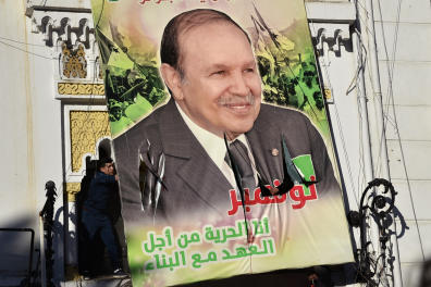Algerian demonstrators tear down a large billboard with a picture of their current President Abdelaziz Bouteflika on it, during a demonstration against his candidacy for a fifth term, on February 22, 2019 in Algiers. - Several hundred demonstrators, in defiance of a ban on protests, rallied in the Algerian capital today against a bid by ailing President Abdelaziz Bouteflika for a fifth term, an AFP correspondent said. (Photo by RYAD KRAMDI / AFP)