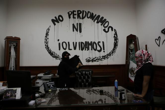 Des « black blocs», devant un grafitti« Nous ne pardonons pas et n'oublions pas»dans un bureau de la CNDH, le 10 septembre à Mexico.