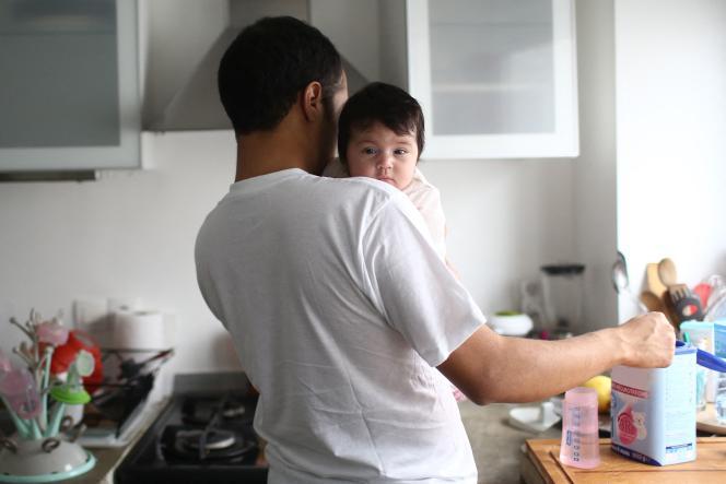 Un papa prépare le biberon de son bébé.