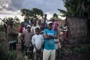 Dhera residents stand in front of a house that have been burnt down in a retaliation attack in April allegedly committed by Congolese military in the Dhera village, Ituri province, northeastern Democratic Republic of Congo, on September 15, 2020. Since the end of 2017, the conflict in Ituri has left several hundred people dead and more than one and a half million displaced. Most of the massacres are attributed to armed militias belonging to the Lendu community and claiming to defend themselves against the Congolese army and the Hema community. / AFP / ALEXIS HUGUET