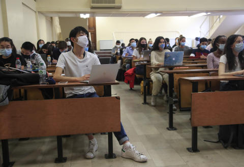Students of the Pantheon university wearing face masks to prevent the spread of coronavirus attend a class in Paris, Thursday, Sept. 24, 2020. Dozen of COVID-19 clusters have emerged since French campuses and classrooms opened this month. The clutches of cases are a warning sign for countries elsewhere in Europe, where most universities are readying to resume teaching and research in coming weeks. (AP Photo/Michel Euler)
