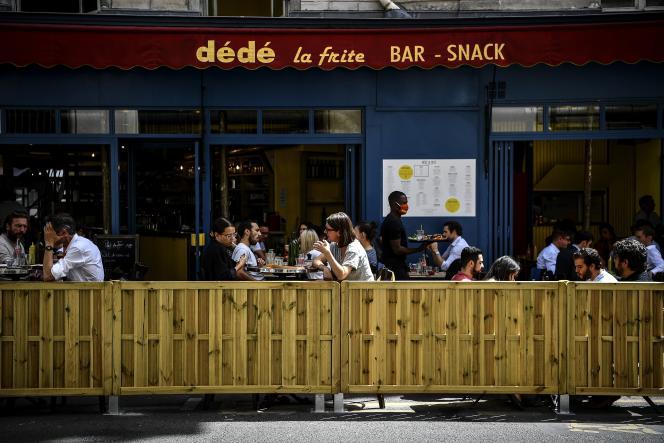 Devant un restaurant, à Paris, le 23 juillet.