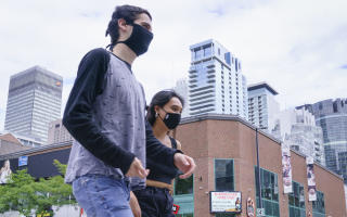 Pedestrians wearing protective masks walk down Montreal's Sainte-Catherine Street, on Tuesday, Sept. 1, 2020. The Quebec government has expressed its concern over an increasing number of COVID-19 cases in the province. (Paul Chiasson/The Canadian Press via AP)