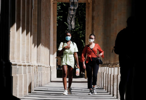 Women wearing protective masks walk in the Palais Royal as France reinforces mask-wearing as part of efforts to curb a resurgence of the coronavirus disease (COVID-19) across the country, in Paris, France August 6, 2020. REUTERS/Gonzalo Fuentes - RC2E8I9SPRHW