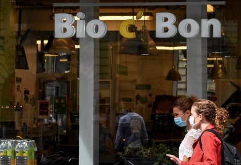 People walk by a Bio C'Bon store, on September 8, 2020, in Paris. The retailer specialized in organic food Bio C'Bon has been placed into receivership by Paris' trade court on September 8, 2020, the group announced the same day. / AFP / ALAIN JOCARD
