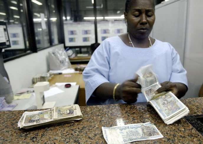Une salariée de la Banque centrale des Etats de l'Afrique de l'Ouest (BCEAO) en train de compter des francs CFA, en septembre 2004 à Abidjan.