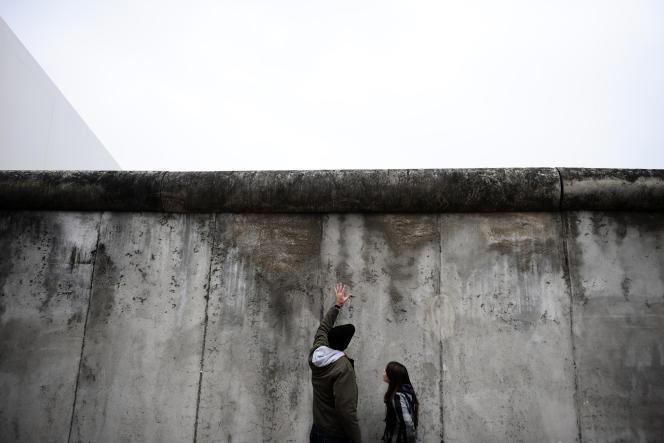 Des gens regardent un segment préservé du Mur de Berlin (1961-1989) au mémorial situé sur Bernauer Strasse, en Octobre 2009.