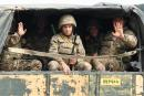Servicemen of Karabakh's Defence Army wave while riding in the back of a truck on the way to the town of Martakert during fighting with Azerbaijan over the breakaway Nagorny Karabakh region on September 29, 2020. / AFP / Narek Aleksanyan