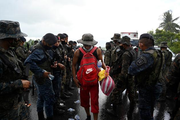 Un migrant hondurien, devant des membres de l'armée guatémaltèque, à Entre Rios, au Guatemala, après avoir traversé la frontière du Honduras, le 1eroctobre 2020.
