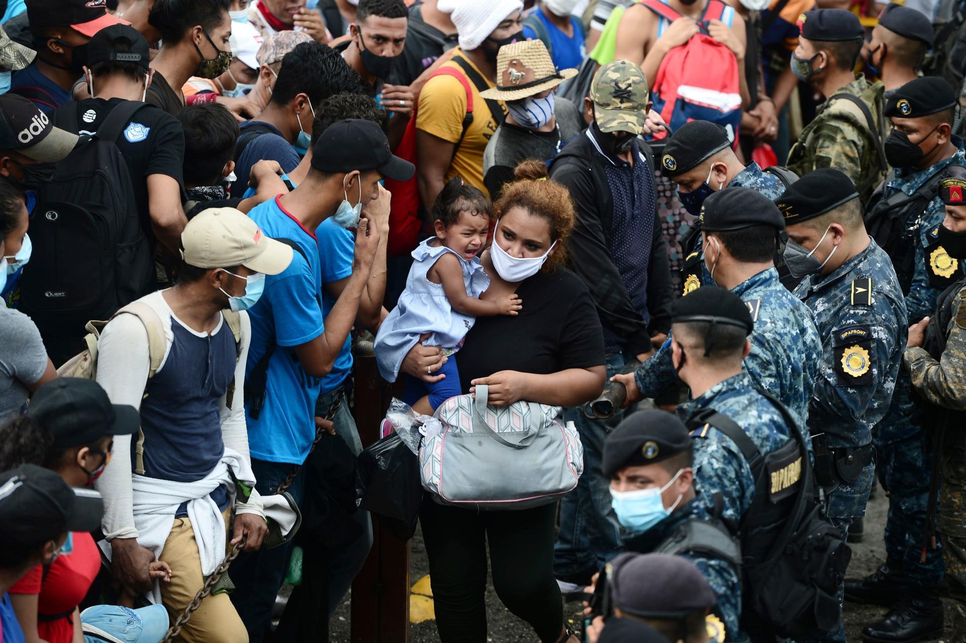 Des migrants honduriens franchissent la barrière de police pour entrer au Guatemala en route pour les Etats-Unis, à la frontière de Corinto, au Honduras, le 1eroctobre.