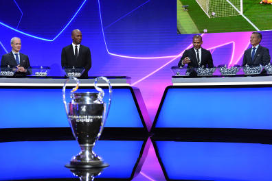 """This handout picture taken and released by UEFA on October 1, 2020, shows Ivorian former international Didier Drogba (2nd L) picking a ball next to UEFA competitions director Giorgio Marchetti (L), French international Florent Malouda (2nd R) and UEFA Head of Club Competitions Michael Heselschwerdt during the UEFA Champions League group stage draw at the RTS studios in Geneva. (Photo by Harold Cunningham / UEFA / AFP) / RESTRICTED TO EDITORIAL USE - MANDATORY CREDIT """"AFP PHOTO / UEFA / HAROLD CUNNINGHAM"""" - NO MARKETING NO ADVERTISING CAMPAIGNS - DISTRIBUTED AS A SERVICE TO CLIENTS"""
