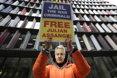 A demonstrator holds a banner and wears a Julian Assange mask opposite the Old Bailey in London, Thursday, Oct. 1, 2020, as the Julian Assange extradition hearing to the US continues. (AP Photo/Kirsty Wigglesworth)