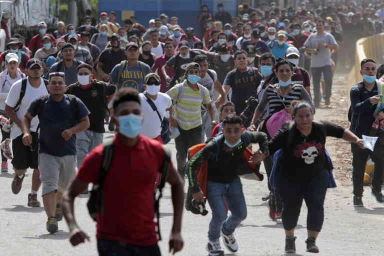Migrants attempt to cross the border from Corinto, Honduras, into Corinto, Guatemala, Thursday, Oct. 1, 2020. Hundreds of migrants walked from San Pedro Sula, Honduras to the Guatemala border, testing a well-trod migration route now in times of the new coronavirus. (AP Photo)