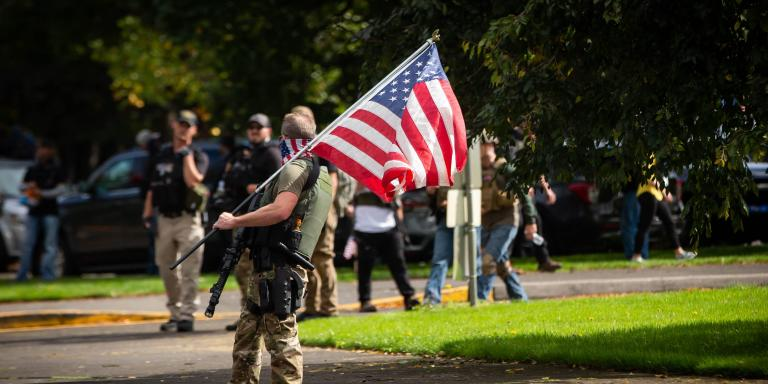 An armed atteendee skateboards waving an american flag as members of the Proud Boys and other similar groups attend a rally at Delta Park in Portland, Oregon on September 26, 2020. Far-right group