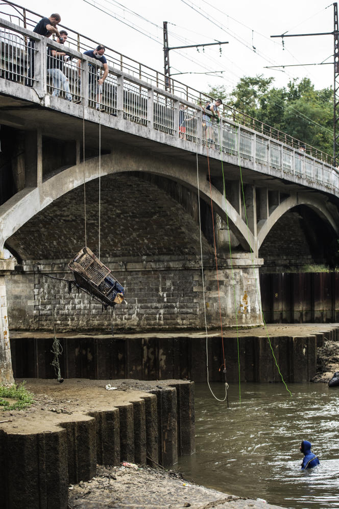 Les membres de l'association Pêche Aveugl'Aimant extirpent un chariot de supermarché de la rivière Huisne, au Mans, le 19 septembre.