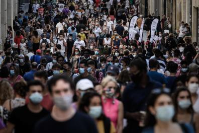 Pedestrians, some of them wearing protective face masks due to the COVID-19 coronavirus pandemic, walk in a street lined with shops in Bordeaux, southwestern France, on September 5, 2020. / AFP / PHILIPPE LOPEZ