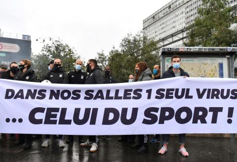 """Demonstrators stand with a banner which translates as """" in our gyms there is only one virus - that's sport"""" as they take part in a rally in Paris on October 2, 2020, in protest at the closure of gymnasiums as the pandemic coronavirus (Covid-19) continues to spread across France. / AFP / Alain JOCARD"""
