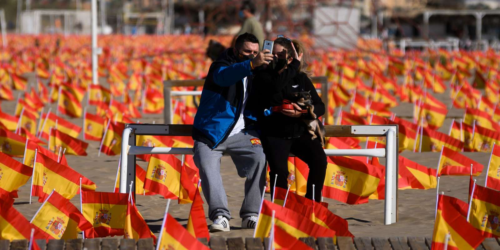 TOPSHOT - A couple take a selfie photo as they sit among thousands of Spanish flags, representing the Spanish victims of COVID-19, on Patacona beach in Valencia, on October 4, 2020. Spain has so far claimed more than 32,000 lives and 790,000 infected in the highest infection rate in the European Union. / AFP / Jose Jordan