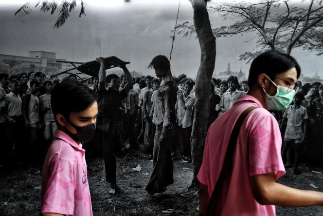 Deux étudiants devant une photo du massacre du 6 octobre 1976 à l'université Thammasat, à Bangkok, le 6 octobre 2020.