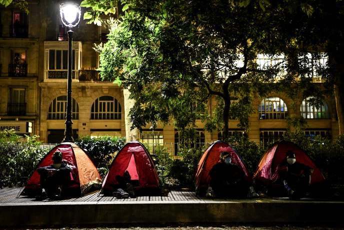 De jeunes migrants sont assis près de leurs tentes, dans un camp de fortune, mis en place par des bénévoles de Médecins sans frontières (MSF) et Utopia56 dans un parc public à Paris, le 29juin2020.