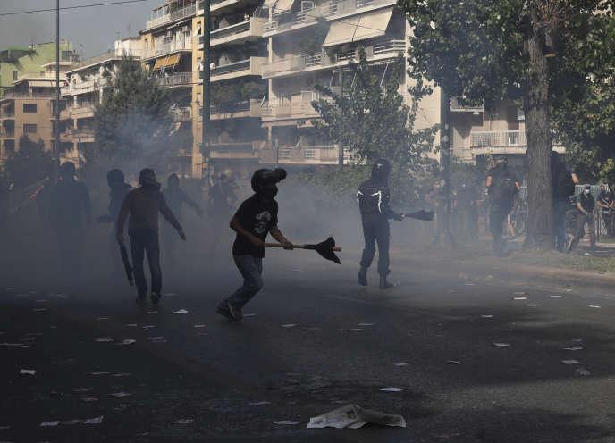 Les manifestants sont debout au milieu des gaz lacrymogènes tirés par la police antiémeute lors d'échauffourées dans le cadre d'un rassemblement antifasciste, devant le palais de justice d'Athènes, à la suite de l'annonce du verdict du procès du fondateur d'Aube dorée, mercredi 7 octobre 2020.