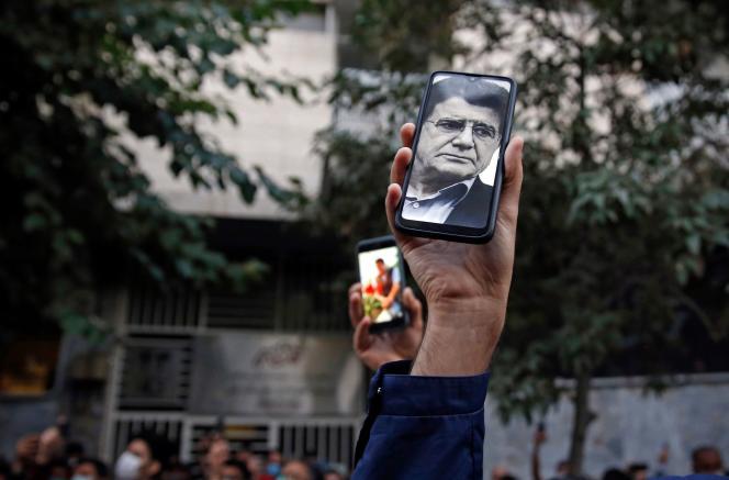 Les fans du chanteur, instrumentiste et compositeur iranien Mohammad-Reza Shajarian affichent ses photos sur leur téléphone alors qu'ils se rassemblent devant l'hôpital Jam, à Téhéran, où il est mort le 8 octobre 2020.
