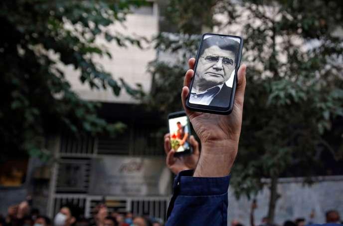Les fans du chanteur, instrumentiste et compositeur iranien Mohammad-Reza Shajarian regardent ses photos sur leurs téléphones alors qu'ils se rassemblent devant l'hôpital Jam à Téhéran, où il est décédé le 8 octobre 2020.