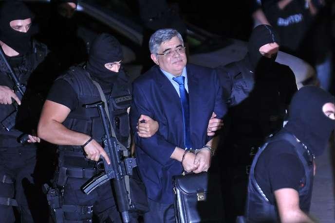 Le secrétaire général du parti néonazi Aube dorée,Nikolaos Michaloliakos, escorté par des policiers, le 2octobre2013.