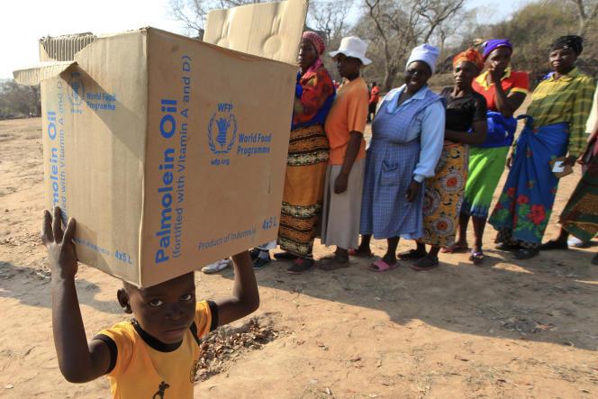 Un enfant porte un carton de rations distribué par le PAM, dans le district de Mwenezi, au Zimbabwe, le 9septembre 2015.