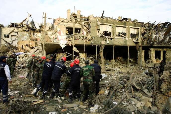 Les membres d'une équipe de secours dans le quartier visé par des tirs de roquettes dans la grande ville de Gandja, en Azerbaïdjan, le 11 octobre.