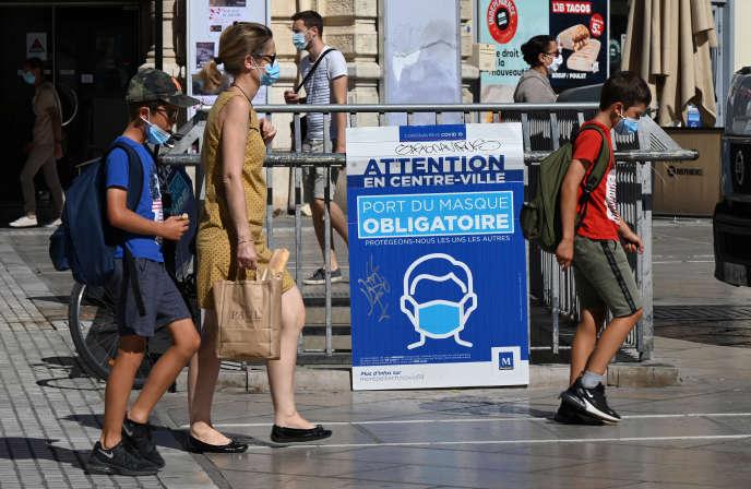 Des personnes portant un masque marchent à côté d'un panneau d'affichage portant l'inscription «Masque obligatoire dans le centre-ville de Montpellier», le 25août2020.