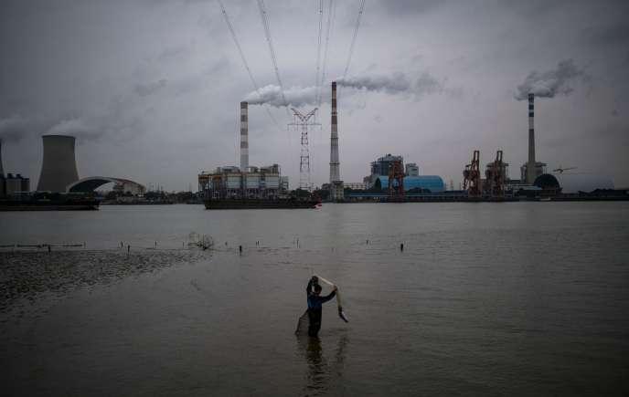 Un pêcheur, dans le fleuve Huangpu, devant la centrale électrique au charbon de Wujing, à Shanghai en 2017.