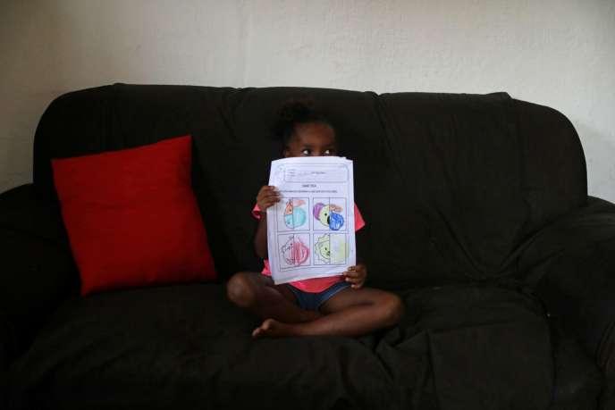 Une écolière de 5 ans et son devoir effectué à la maison dans le bidonvillePrazeresde Rio de Janeiro, le 1er octobre.