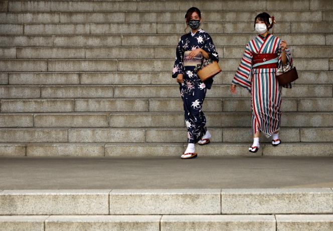 Deux femmes portent le masque devant le temple du quartier d'Asakusa, à Tokyo, le 13 octobre.