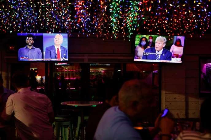 Un restaurant de Tampa, en Floride, diffuse sur deux écrans les « réunions publiques» en direct de Joe Biden et Donald Trump, jeudi 15octobre.