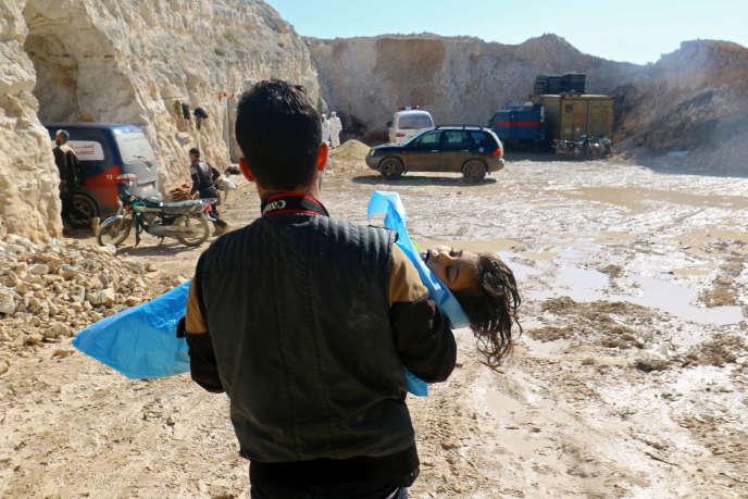 Un homme porte le corps d'un enfant mort, après ce que les secouristes ont décrit comme une attaque au gaz présumée dans la ville de Khan Sheikhoun à Idlib, en Syrie, tenue par les rebelles, le 4 avril 2017.