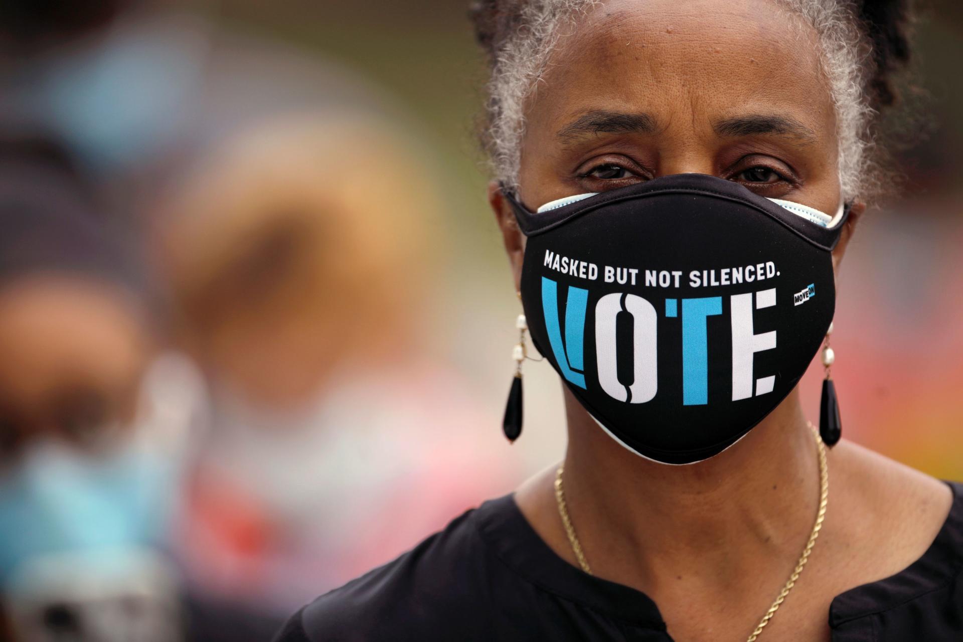 Une femme porte un masque avec un message exhortant à la participation électorale alors qu'elle fait la queue pour voter le 15 octobre, premier jour des élections anticipées, à Durham, en Caroline du Nord.