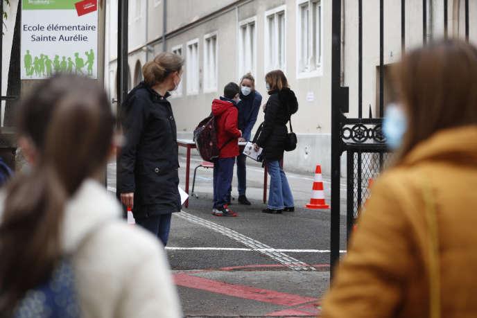 Un enseignant accueille des écoliers dans une école de Strasbourg, dans l'est de la France, le jeudi 14 mai.