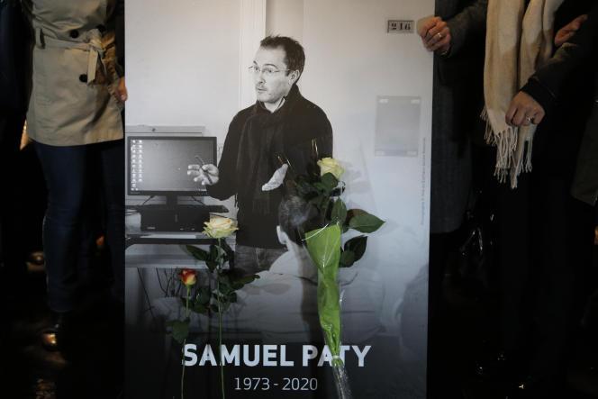 Des personnes portent la photo de Samuel Paty, le 20 octobre, lors d'une marche àConflans-Sainte-Honorine (Yvelines).