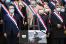 National Assembly president Richard Ferrand (L) and French right wing Les Republicain MP Marc Le Fur (2R) stand among French MPs near a photo of late teacher Samuel Paty, as they pay tribute on October 20, 2020, in front of the Palais Bourbon, French national assembly, in Paris, to slain history teacher Samuel Paty, who was beheaded by an attacker for showing pupils cartoons of the Prophet Mohammed in his civics class, on October 16, 2020, in Conflans-Sainte-Honorine, northwest of Paris. Paty, 47, was attacked on October 16 on his way home from the junior high school where he taught by 18-year-old Chechen man Abdullakh Anzorov, who was shot dead by police. Following the attack, tens of thousands of people took part in rallies countrywide to honour Paty and defend freedom of expression. / AFP / Christophe ARCHAMBAULT
