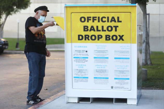 Le 14 octobre, un piéton dépose son bulletin de vote par correspondance sur une urne officielle devant un bureau de Norwalk, en Californie.