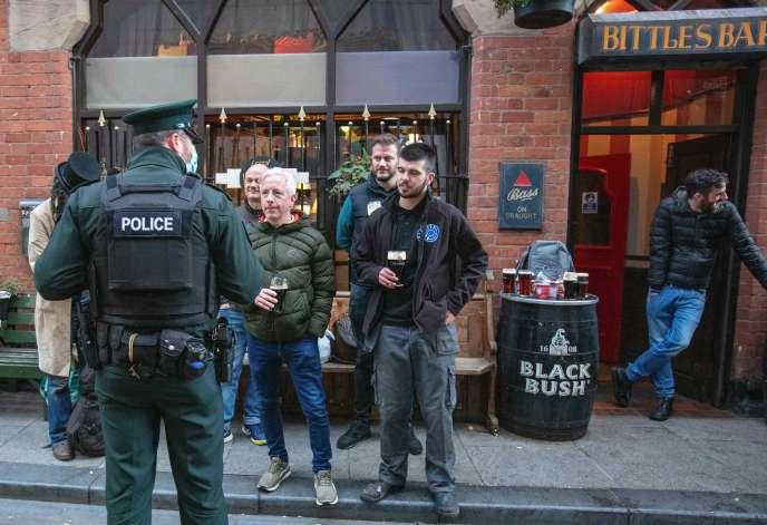 Un agent de police veille au respect des règles sanitaires à Belfast, dans le nord de l'Irlande, le 16 octobre.