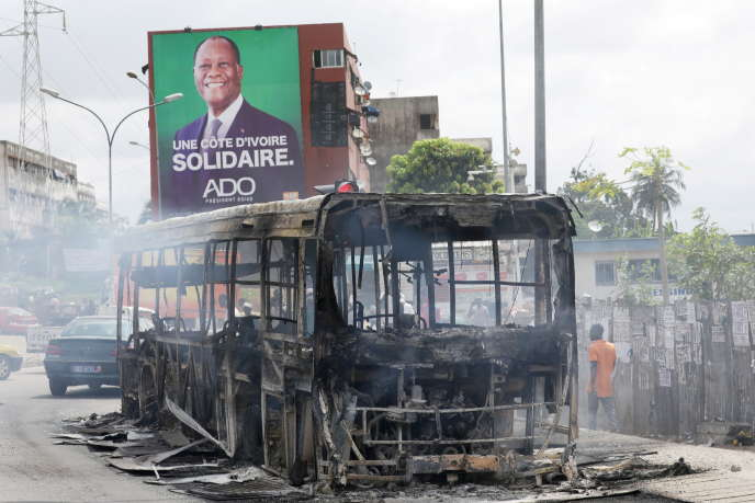 Carcasse d'un bus incendié par des manifestants qui protestaient contre la décision du président Alassane Ouattara de se présenter pour un troisième mandat, à Abidjan, le 19 octobre 2020.
